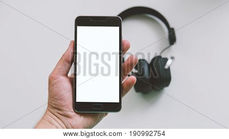 Wireless headphones are black for the music fan of the clown-up. External headphones lying on a white background. Connecting headphones to your smartphone