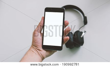 External Earphones And Telephone On White Background With Close-up.