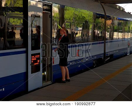 Woman.conductor. Lodz, Poland - June 02, 2017 Woman conductor gives the signal for the departure of the train from the railway station Lodz Widzew.