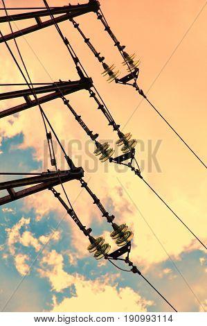 Electrical power insulator taken closeup against of sunset sky.