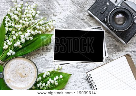 vintage retro camera with blank photo frames to put your pictures blank notebook and coffee cup with lily of the valley flowers bouquet over white wooden table. top view. mock up