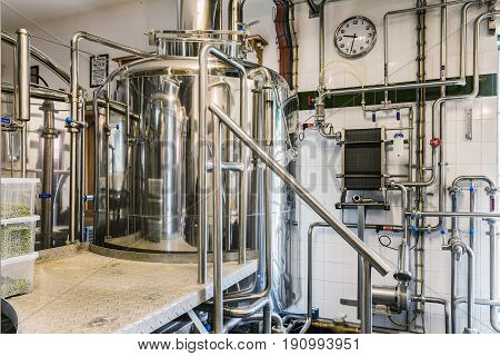 Modern beer plant (brewery) with brewing kettles vessels tubs and pipes made of stainless steel. Small home brewery.