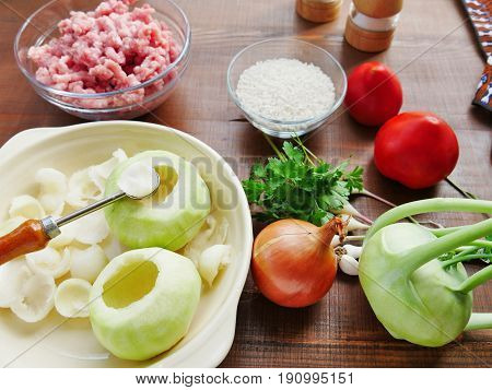 Ingredients for cooking stuffed kohlrabi on wooden table