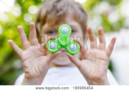 School kid playing with Tri Fidget Hand Spinner outdoors. Popular and trendy toy for hands for children and adults. Selective focus on hands of boy