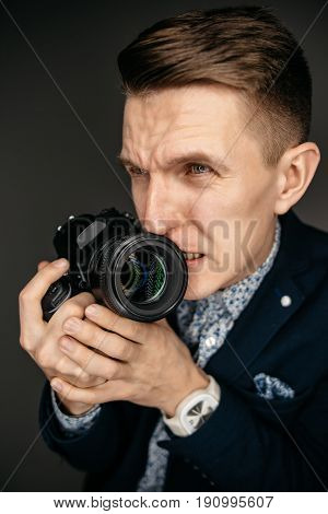 Portrait of a young photographer with a camera in his hands, with a nervous expression on his face. Studio shot