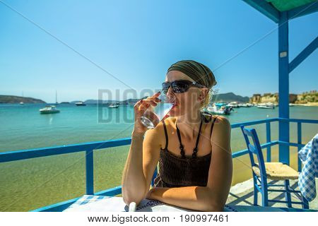Woman drinking fresh water or lime juice at Methoni Beach. Female is looking away while sitting at an outdoor restaurant. Methoni Castle on background, Peloponnese, Greece. Europe summer vacation.