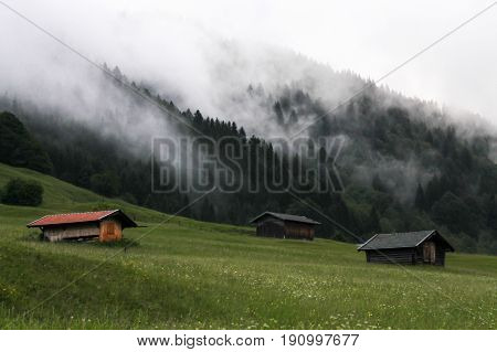 dimensions three houses on grass forest breath fog in Gerold village Bavaria Germany Alps