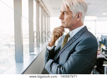 Side view shot of mature businessman standing beside office window looking outside and thinking with hand on chin. Senior professional thinking for solutions.