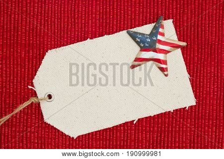 A cloth gift tag with a retro American flag star on shiny red material that is blank for your message