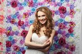 Beautiful woman smiling, wearing a wedding dress, on a background of flowers. Emotion shyness poster