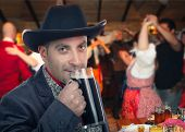 Forty years old man in black cowboy hat drinks glass of stout beer. Farmer wearing dark gray jacket stands on blurred background of dancers in western saloon. Medium close-up horizontal portrait. poster