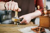 Closeup shot of barista working in coffee shop: pressing fresh grains with tamper after grinding them in antique mill poster