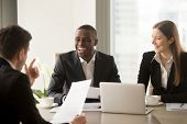 Handsome afro american businessman with beaming smile laughing on multi-ethnic international team meeting when partner telling joke, cheerful diverse business people having fun friendly atmosphere poster