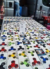 Fidget Spinners. Waterloo, Belgium - June 11, 2017. A vendor sells fidget spinners at an outdoor farmers market