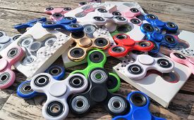Fidget Spinners. Waterloo, Belgium - June 11, 2017. A pile of assorted colorful fidget spinners on a rustic wood table. The popular hand spinner toys have become a worldwide trend.
