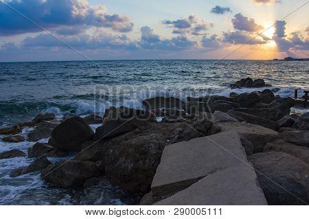 Landscape of the sundown in sea water amongst rocky beach poster