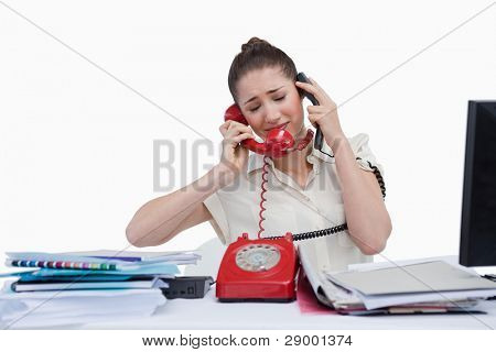 Overburden businesswoman answering the phones against a white background