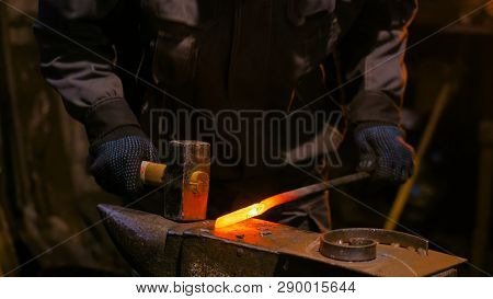 Professional blacksmith forging molten metal on anvil at smithy, workshop. Handmade, craftsmanship and blacksmithing concept poster