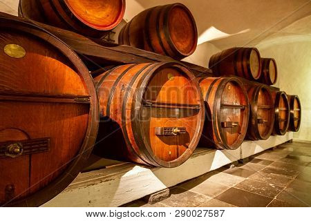 Old Wine Cellar. Pile Of Wine Barrels In A Wine Cellar. Old Wooden Barrels With Wine In A Wine Vault