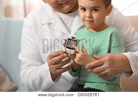 Doctor Measuring Patient's Blood Sugar Level With Digital Glucose Meter At Home, Closeup. Diabetes C