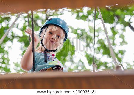 Cute Little Funny Caucasion Blond Girl In Helmet Having Fun Walking By Rope Suspension Bridge In Adv