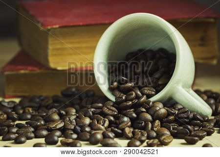 Coffee Bean In Tilted Ceramic Cup And Old Book Laid Behind On Wooden Table With Morning Light.