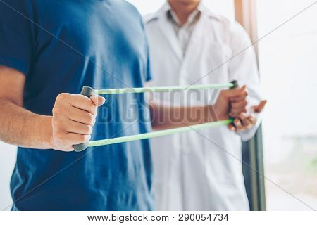 Physiotherapist Man Giving Resistance Band Exercise Treatment About Chest Muscles And Shoulder Of At