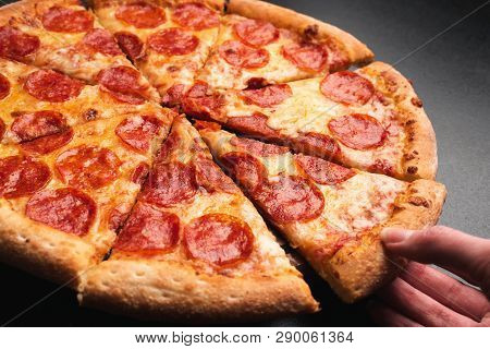 Taking Slice Of Pepperoni Pizza. Tasty Pepperoni Pizza On Black Background, Closeup View. Hand Takin
