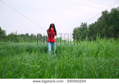 Girl With Covered Face Stands In The Middle Of The Swamp
