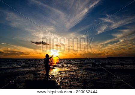 Feminine Silhouette On Sunset Background, Waterand Wind