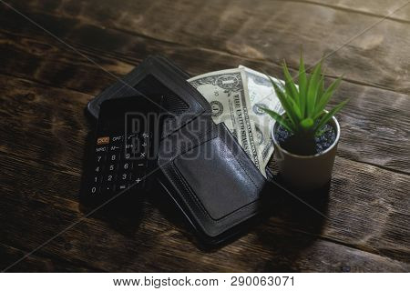 Calculator, wallet and a few dollars on a table. Tight of money. Lack of money. Financial problems. Bankrupt. Pay the debts concept. poster