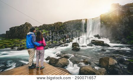 Couple Travelers Travel To Oxararfoss Waterfall In Thingvellir National Park, Iceland. Oxararfoss Wa