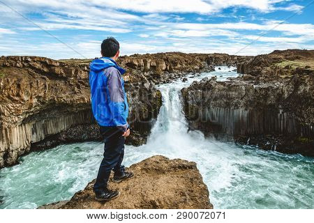 poster of Traveler hiking in Icelandic summer landscape at the Aldeyjarfoss waterfall in north Iceland. The waterfall is situated in the northern part of the Sprengisandur Road within the Highlands of Iceland.