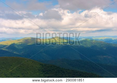 Mountain Landscape With Cloudy Sky. Peaks Of Distant Ridge In Sunlight. Beautiful Nature Background