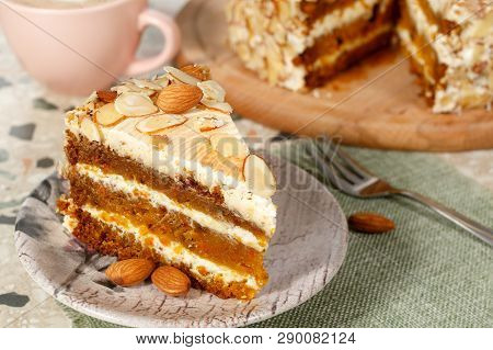 Close-up The Slice  Of Vegetarian Carrot Cake With Almonds On A Saucer And A Fork Near. Pink Cup Of