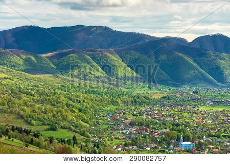 Mountainous Countryside In Springtime. Village In The Valley, Mountain Ridge With Spots Of Snow. Sun