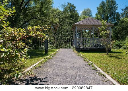 Path Leading To Wooden Summerhouse Standing Among Lush Green Trees And Shrubs On Bright Sunny Summer