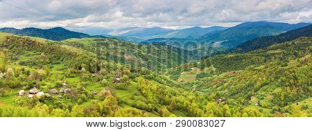 Panorama Of Mountainous Countryside In Springtime. Village On The Hillside, Mountain Ridge In The Di