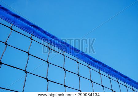 Fragment Of Volleyball Net Against Clear Blue Sky Background. Copy Space