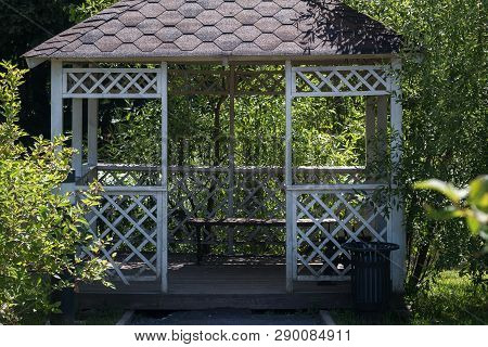 Entrance Of White Wooden Summerhouse Surrounded By Lush Green Trees On Bright Sunny Summer Day