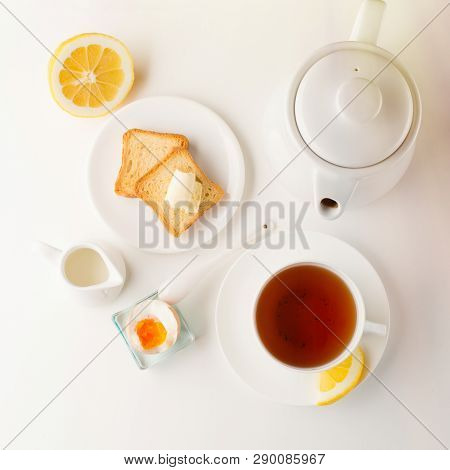 Breakfast Table With Soft Boiled Egg, Crispy Toasts And Cup Tea On Whiite Background, Top View