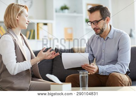 Young Woman Explaining Her Problem To Counselor Making Notes On Paper During Psychological Session O