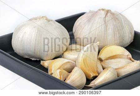 Raw And Unpeeled Garlic Gloves On Balck Dish On White Background