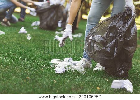 Ecology Protection. Millennials Environmentalists Cleaning Park, Collecting Garbage From Grass, Empt