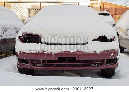 Front Of Abandoned Car Covered With Snow
