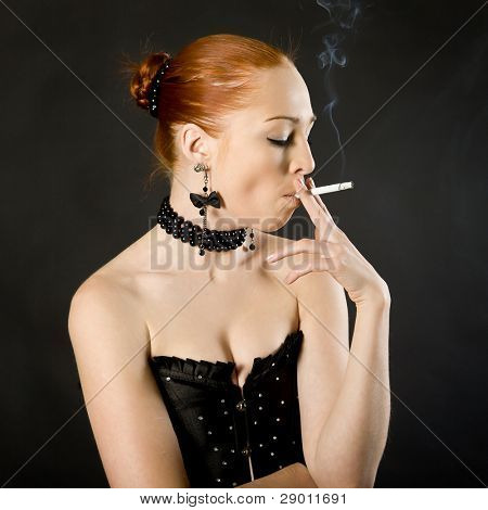 young elegant girl with a cigaret on a black background