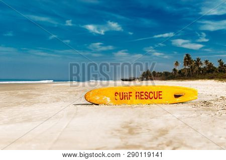Bright Yellow Surfboard In The Form Of A Pointer With A Red Word Rescue On A Sandy Beach In The Afte