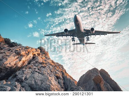 Big Airplane Is Flying Over Rocks At Sunset In Summer. Landscape With  Landing Passenger Airplane, M