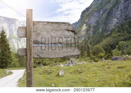 Wooden Signpost In Mountain Landscape.