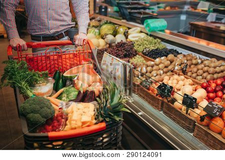 Young Man Alone In Grocery Store. Cut View Guy Hold Trolley Hand. Basket Full Of Vegetables And Frui